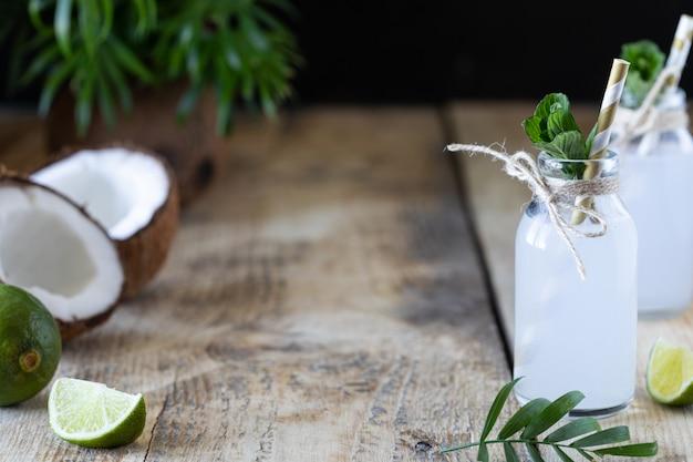 Acqua di cocco fresca in bottiglia di vetro sul tavolo. bevanda vegetariana. copia spazio Foto Premium