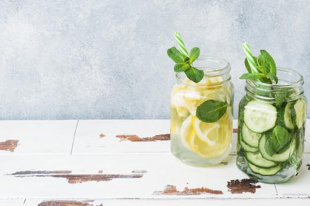 Acqua dolce in barattolo con limone, cetriolo e menta sul tavolo di legno. copia spazio Foto Premium