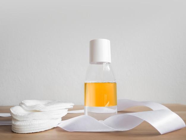 Acqua olio a due fasi micellare con tamponi di cotone sul tavolo di legno e parete bianca. Foto Premium
