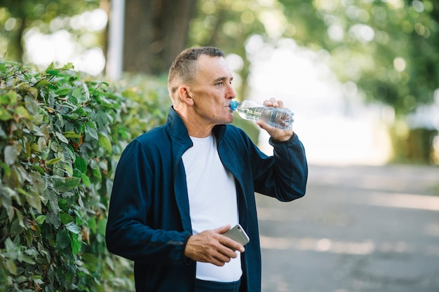 Acqua potabile dell'uomo anziano in parco Foto Gratuite