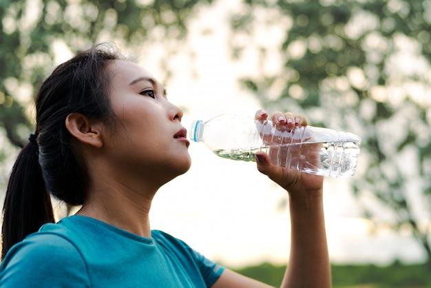 Acqua potabile della donna di forma fisica asia dopo avere corso Foto Premium