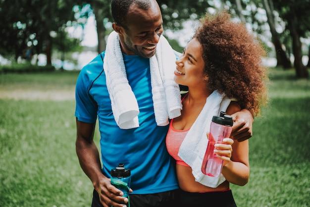 Acqua potabile della donna dopo le coppie di esercizio insieme in parco Foto Premium