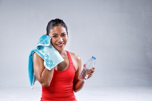 Acqua potabile della donna indiana abbastanza sportiva dopo l'allenamento di yoga su fondo concreto Foto Premium