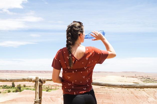 Acqua potabile della donna nel paesaggio del deserto da dietro Foto Gratuite