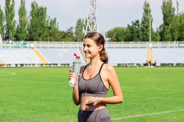 Acqua potabile della ragazza dalla bottiglia dopo essere corso allo stadio. Foto Premium
