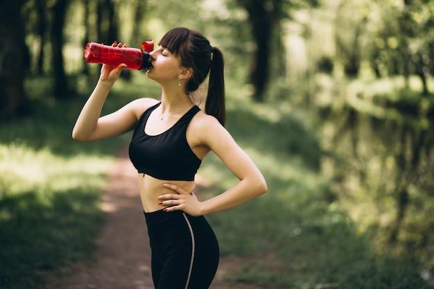 Acqua potabile della ragazza sportiva in parco Foto Gratuite