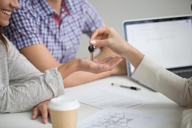 Acquisto del concetto della nuova casa, agente immobiliare che fornisce le chiavi alle coppie, primo piano Foto Gratuite