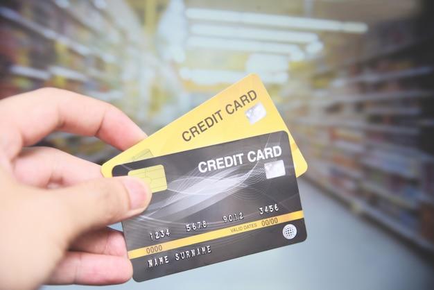 Acquisto della carta di credito nel supermercato - passi il pagamento con carta di credito della tenuta Foto Premium