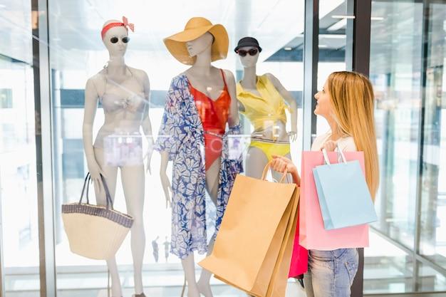 Acquisto della finestra della bella donna nel centro commerciale Foto Gratuite