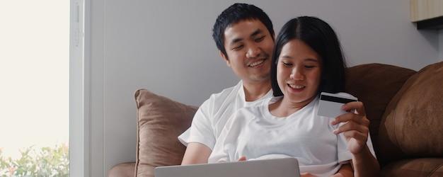 Acquisto online delle giovani coppie incinte asiatiche a casa. mamma e papà sentirsi felici utilizzando la tecnologia del computer portatile e il prodotto d'acquisto del bambino della carta di credito mentre si trovano sul sofà in salone a casa. Foto Gratuite