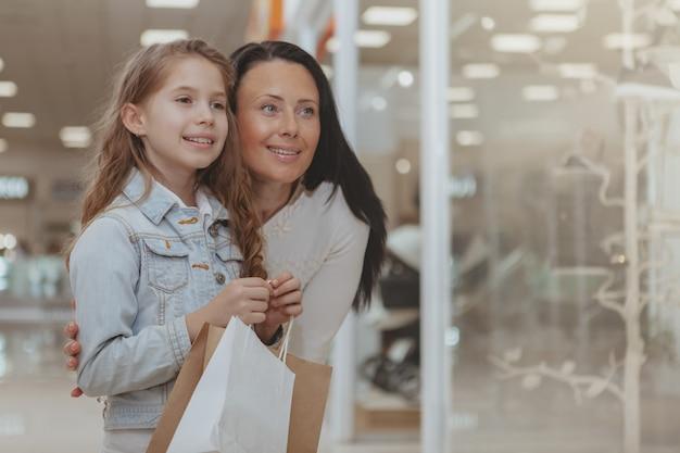 Acquisto sveglio della bambina al centro commerciale con sua madre Foto Premium