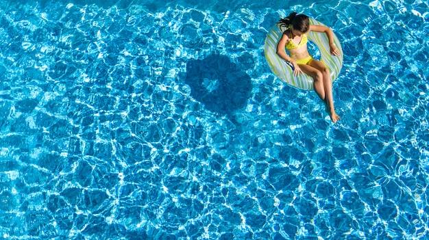 Acrive ragazza in piscina vista aerea dall'alto dall'alto, il bambino nuota sulla ciambella ad anello gonfiabile, il bambino si diverte in acqua blu sulla località di vacanza per famiglie Foto Premium