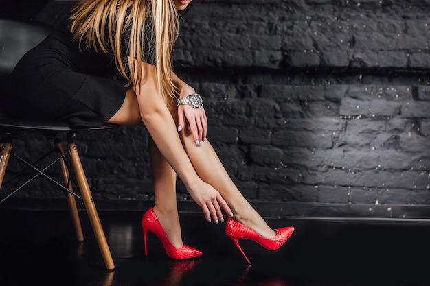 Adatti il ritratto del primo piano, giovane donna elegante. abito corto nero, seduto in poltrona, studio isolato colpo, piede. Foto Premium