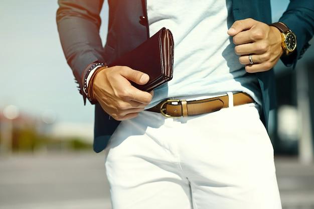 Adatti il ritratto dell'uomo di modello bello del giovane uomo d'affari nel vestito casuale del panno con gli accessori sulle mani Foto Gratuite
