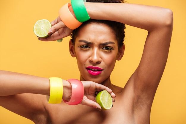 Adatti il ritratto della donna afroamericana con trucco d'avanguardia e gli accessori che tengono le due metà di calce matura fresca in entrambe le mani isolate, sopra la parete gialla Foto Gratuite
