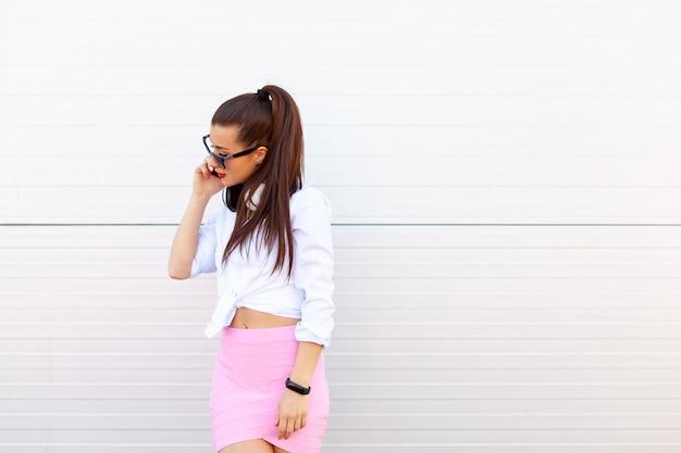 Adatti il ritratto della donna sorridente graziosa in occhiali da sole che parla sullo smartphone contro la parete grigia. Foto Premium