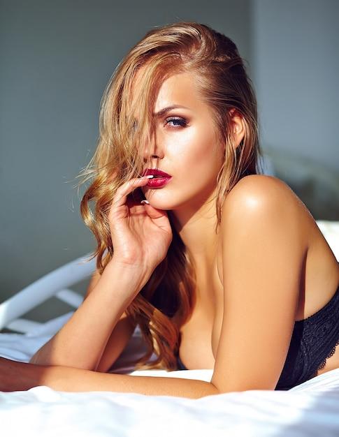 Adatti il ritratto di bello giovane modello biondo sexy della donna adulta che porta la biancheria erotica nera che si trova sul letto al tramonto Foto Gratuite