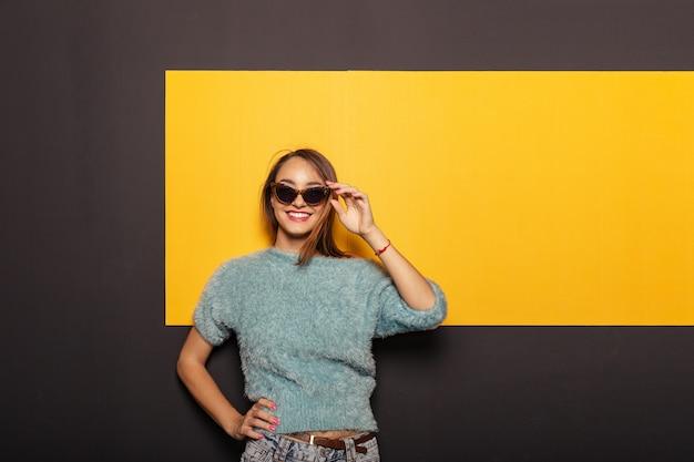 Adatti il ritratto di una donna attraente e alla moda con gli occhiali da sole Foto Gratuite