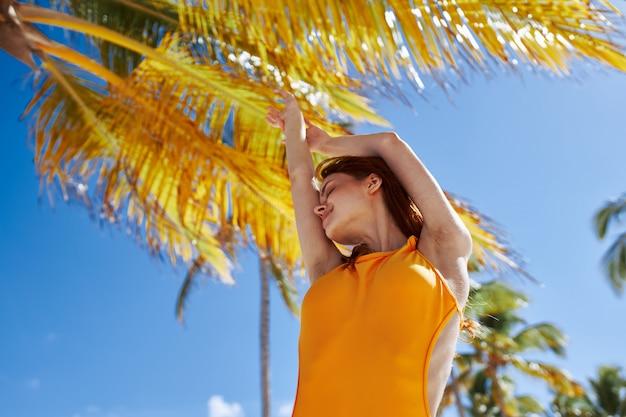 Adatti l'estate del sole del modello della palma, la bella posa di modello Foto Premium