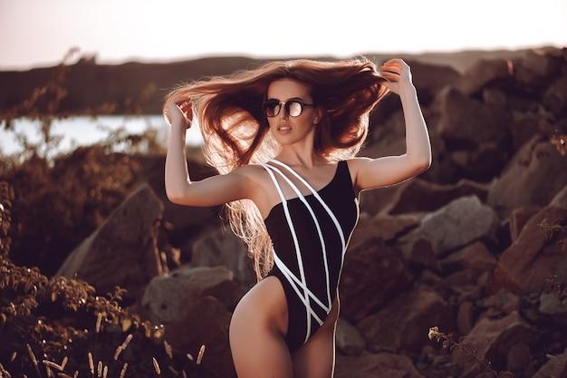 Adatti la donna in costume da bagno nero che si trova sulla spiaggia tropicale. Foto Premium