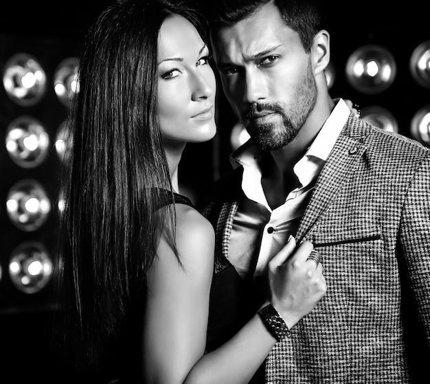 Adatti la foto dell'uomo elegante bello in vestito con la bella donna sexy che posa sul fondo nero delle luci dello studio Foto Gratuite