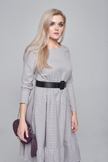 Adatti la foto di bella giovane donna bionda elegante in una borsa della tenuta del vestito grigio che posa sopra la parete grigia. foto di moda primavera estate Foto Premium
