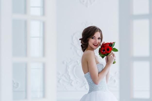 Adatti la foto di bella sposa con il mazzo di fiori in sue mani alla stanza leggera accanto alle porte Foto Premium