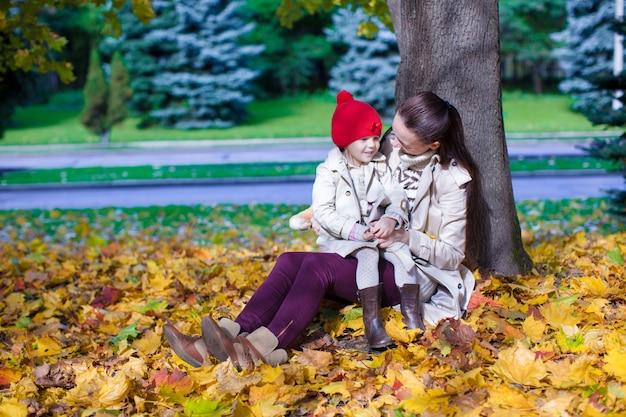 Adatti la giovane madre e la sua piccola figlia adorabile che godono di un giorno soleggiato nel parco di autunno Foto Premium