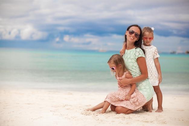 Adatti la madre e due le sue adorabili figlie alla spiaggia esotica il giorno soleggiato Foto Premium