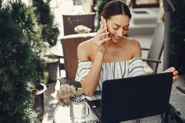 Adatti la ragazza che si siede in un caffè dell'estate Foto Gratuite