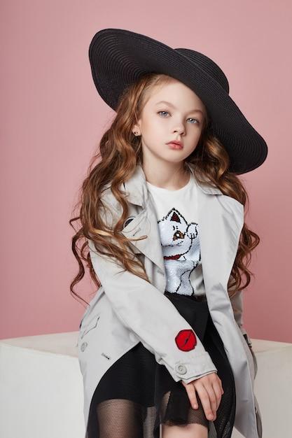 Adatti la ragazza in vestiti alla moda sulla parete colorata Foto Premium