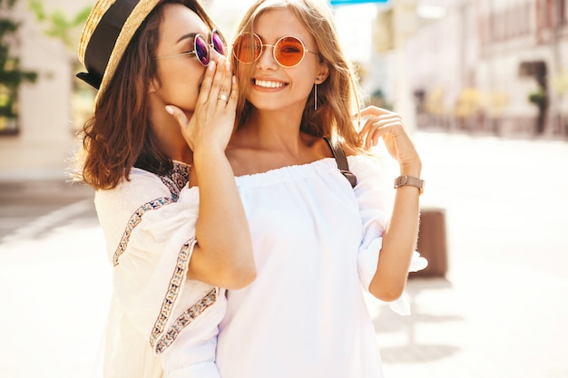Adatti un ritratto di due donne castane e bionde di giovane giovane hippy alla moda nel giorno soleggiato dell'estate nella posa bianca dei vestiti dei pantaloni a vita bassa Foto Gratuite