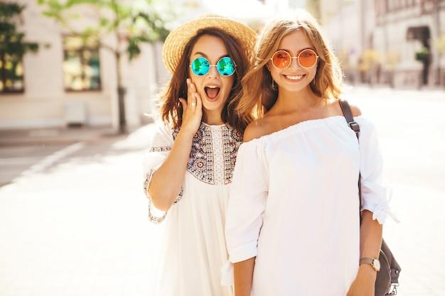 Adatti un ritratto di due modelli alla moda di due giovani donne alla moda del brunette e bionde. le migliori amiche in abito estivo bianco hipster in posa Foto Gratuite