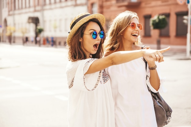 Adatti un ritratto di due modelli di donne castane e bionde di giovane hippy alla moda nel giorno soleggiato dell'estate nella posa bianca dei vestiti dei pantaloni a vita bassa. indicando sulle vendite del negozio Foto Gratuite
