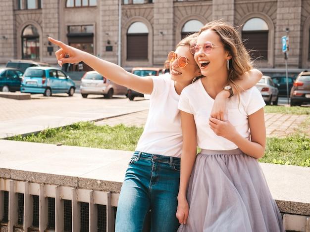 Adatti un ritratto di due modelli di donne castane e bionde di giovane hippy alla moda nel giorno soleggiato dell'estate nella posa bianca dei vestiti dei pantaloni a vita bassa Foto Gratuite