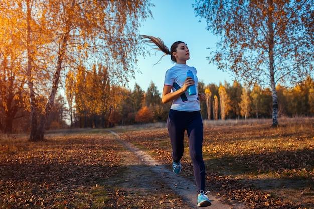 Addestramento del corridore nel parco di autunno. donna che funziona con la bottiglia di acqua e mantenersi in forma al tramonto. stile di vita attivo Foto Premium