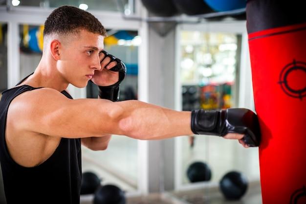 Addestramento dell'uomo con il sacco da boxe Foto Gratuite