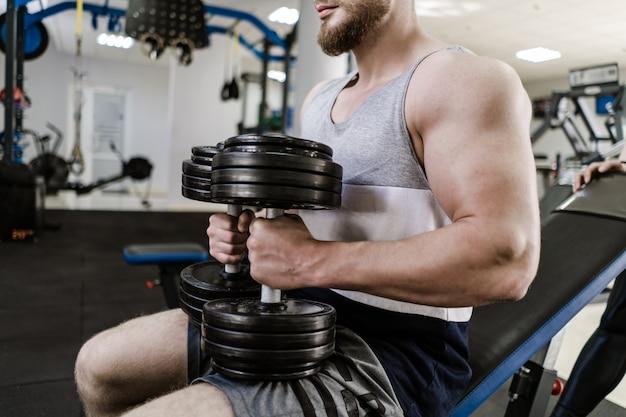 Addestramento muscolare bello dell'uomo con la testa di legno pesante in palestra. il giovane con il grande bicipite si siede e fa allenamento in casa. concetto di sport e salute. Foto Premium