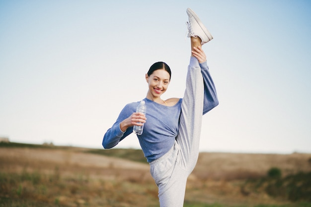 Addestramento sveglio della giovane donna con la bottiglia di acqua Foto Gratuite