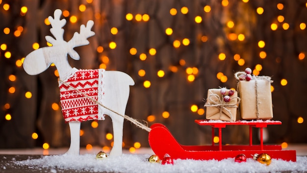 Addobbi natalizi le tue congratulazioni. il cervo nella imbracatura dei regali di capodanno Foto Premium