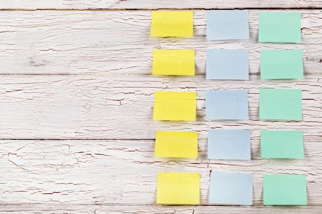 Adesivi gialli, blu e verde appuntati al pavimento in legno bianco Foto Gratuite