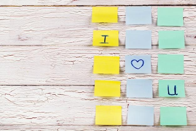 Adesivi gialli, blu e verde con lettere 'i love youn' appuntati al pavimento in legno bianco Foto Gratuite