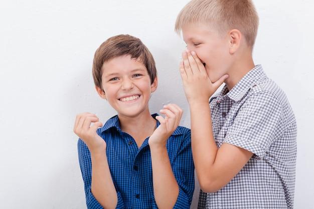 Adolescente che bisbiglia nell'orecchio un segreto all'amico sulla parete bianca Foto Gratuite