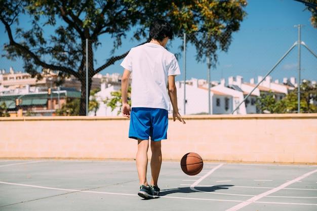 Adolescente che gioca con la palla a corte Foto Gratuite