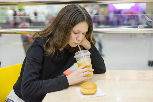 Adolescente che si siede alla tavola che mangia dolce e che beve il succo Foto Premium
