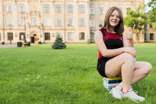 Adolescente che si siede sui libri davanti al liceo Foto Gratuite