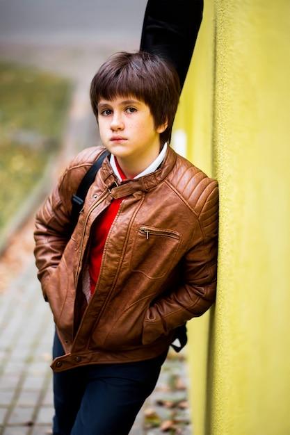Adolescente del ragazzo che propone contro una priorità bassa gialla della parete Foto Premium