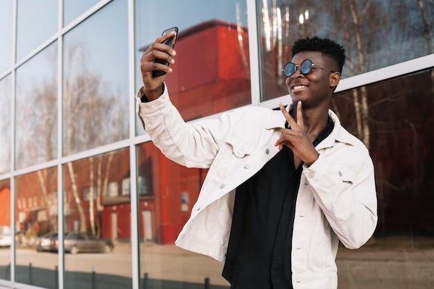 Adolescente felice che prende un selfie all'aperto Foto Gratuite