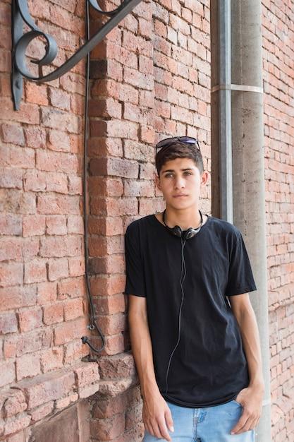 Adolescente serio che si appoggia sul muro di mattoni con la cuffia nera che circonda il suo collo Foto Gratuite