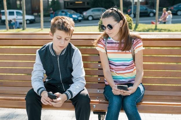Adolescenti della ragazza e del ragazzo che leggono, esaminando lo smartphone Foto Premium